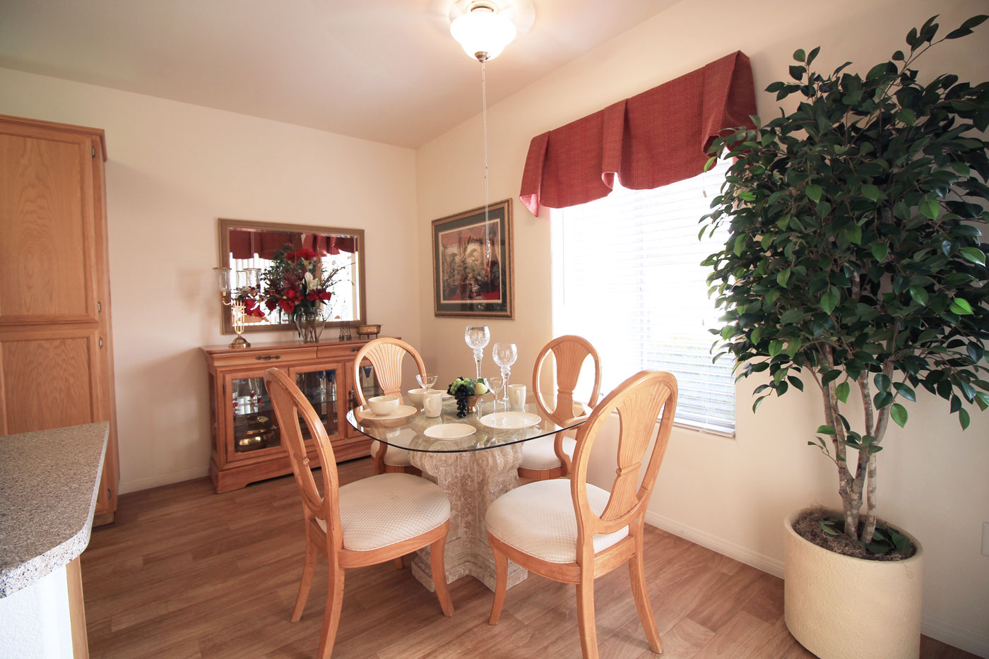 Dining room view with large artificial plant in view.