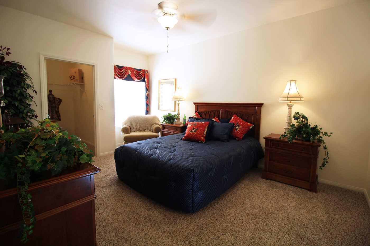 Large bedroom with queen sized bed with navy blue comforter.