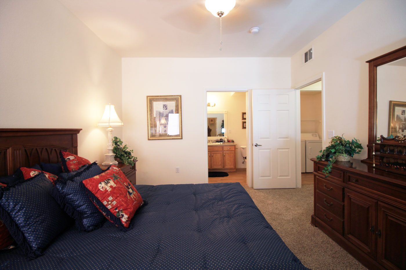 Large bedroom with kind sized bed with a blue comforter and view of bathroom and laundry room.